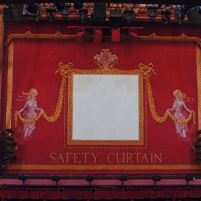 The red Safety Curtain covering the stage at the Alhambra Theatre